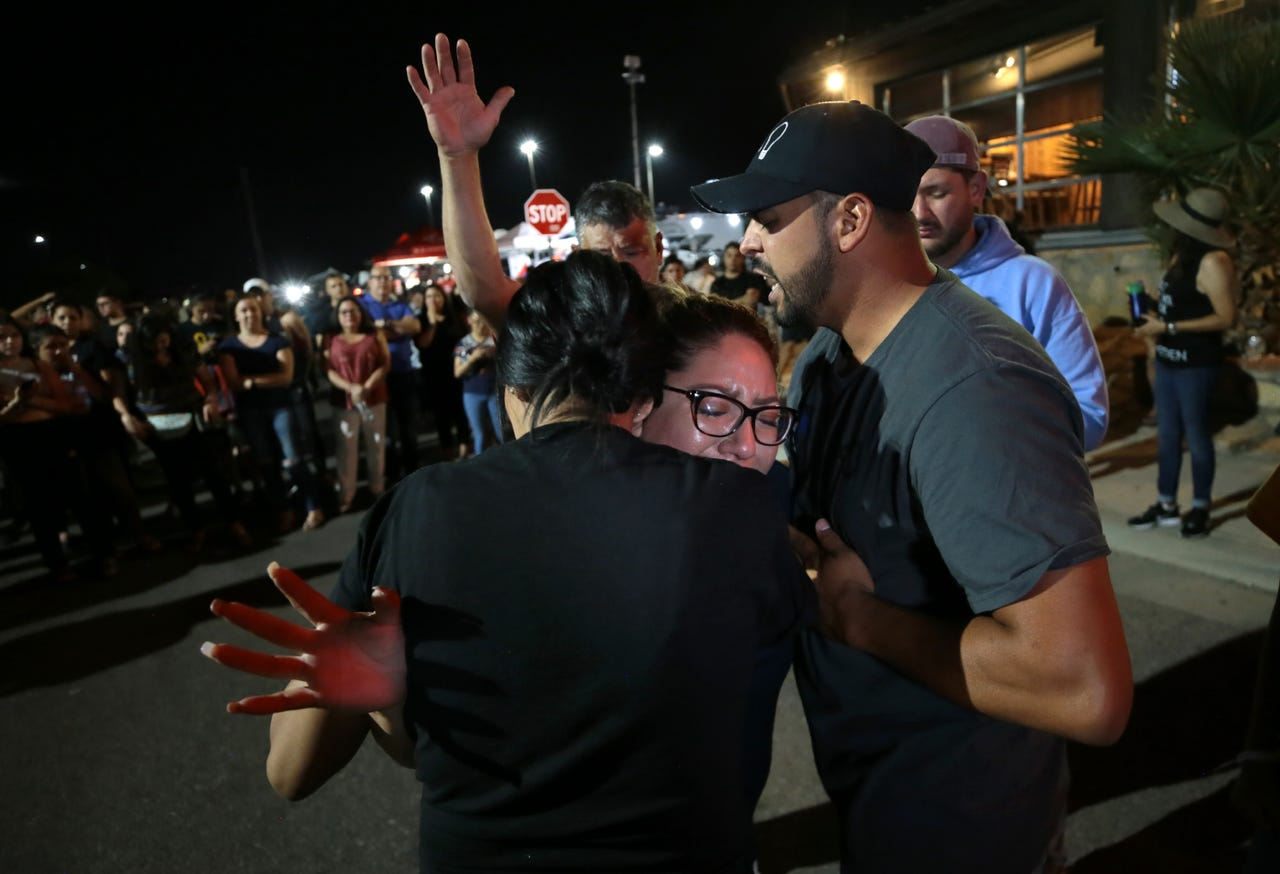 A woman is overcome with emotion as members of the Iglesia Cristiana Manatial en el Desierto pray for her at a memorial Monday, August, 5, 2019, outside the Walmart in El Paso, Texas where Saturday, 22 people were shot and killed and 24 others were wounded. A tragedy like the August, 3, mass murder brought togther an otherwise peaceful community of 700,000; 2 million when you count Juarez.