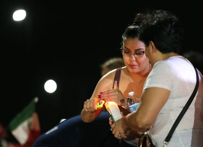 The memorial outside the Walmart in El Paso, Texas, continues to grow Monday, Aug. 5, 2019, as El Pasoans arrive to leave flowers, pray and light candles for the victims of the attack Saturday, Aug. 3, 2019.