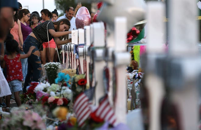 The memorial outside the Walmart in El Paso, Texas, continues to grow Monday, Aug. 5, 2019, as more El Pasoans arrive to leave flowers, pray and light a candle for those killed Saturday, Aug. 3, 2019, when 22 people were killed and 25 were injured.