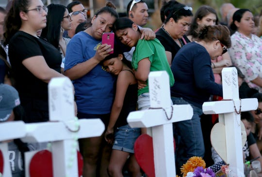 A mothers clings to her daughters as they visit a memorial outside the Walmart in El Paso, Texas on Monday, Aug. 5, 2019. On Saturday, Aug. 3, 2019, 22 people were killed and 25 others were wounded in a mass shooting.