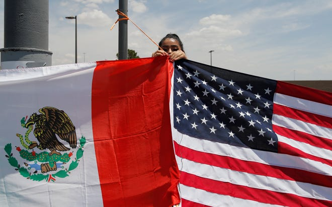 Maylin Reyes hangs a Mexican flag with a U.S. flag at a makeshift memorial Monday, Aug. 5, 2019, near the scene of a mass shooting Saturday, Aug. 3, 2019, at a Walmart in El Paso, Texas.