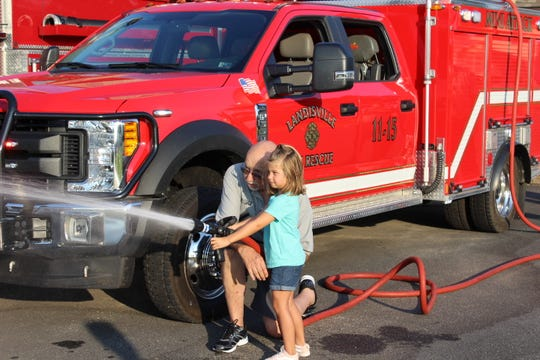 Charles Gazzara, assistant chief, Landisville Volunteer Fire/Rescue Company, shows his granddaughter how to operate a fire hose during the company's open house and family movie night on July 27.