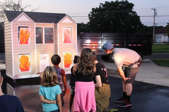 Members of Landisville Volunteer Fire/Rescue Company help community children put out a fire during the company's open house and family movie night on July 27.