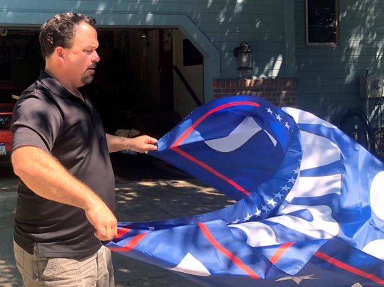 In this July 31, 2019, photo, Jim Noland unspools a Trump flag near Erie, Pa. He cheered Trump on when he tweeted about Rep. Elijah Cummings district anchored in Baltimore. Through Nolan's lens, Trump's message wasn't racist, it was truth. (AP Photo/Claire Galofaro)