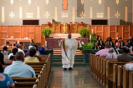 """In this May 27, 2019, Royce Winters, a former police officer and the director of African-American Ministries for the Catholic Archdiocese of Cincinnati, preaches the homily during Mass at the Church of the Resurrection in Cincinnati. Winters said that the fight for equality continues. """"We have to do this together,"""" he said. """"If we don't have our white friends, our white counterparts, to advocate for doing what is right, we won't get past this. (David Gifreda/The Cincinnati Enquirer via AP)"""