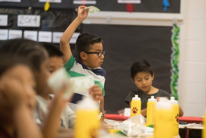 Children in the Lulu Ross Elementary English learners summer camp learn about money Tuesday afternoon at the school. The camp teaches young English learners language fundamentals to help prepare them for the upcoming school year.