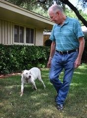 Casper, 11, and his human, Tom Curran, walk in their backyard. Casper was already a mature dog when the Currans adopted him.