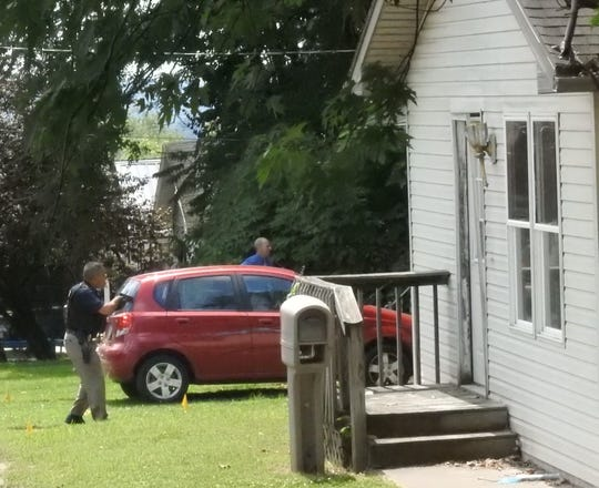 Detectives surround a home in the 500 block of Cliffwood Avenue Monday afternoon following a shooting inside the residence.