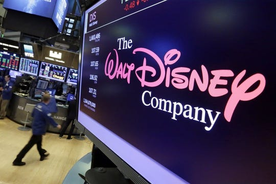 In this Aug. 8, 2017, file photo, The Walt Disney Co. logo appears on a screen above the floor of the New York Stock Exchange. Disney says its net income fell 39% in the latest quarter. Net income for the fiscal third quarter, which ended June 29, 2019, fell to $1.76 billion, from $2.92 billion last year.