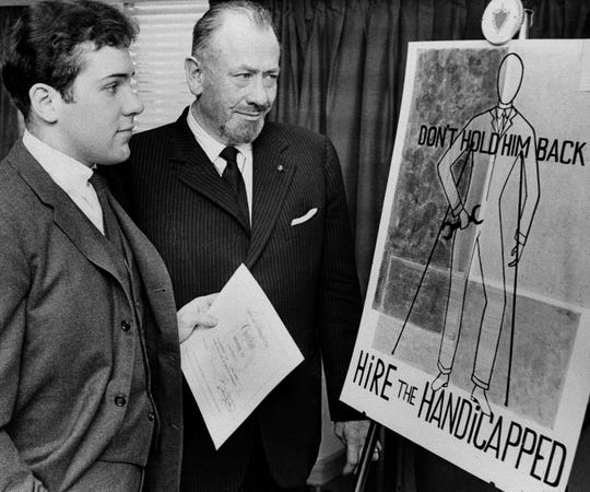 John Steinbeck, right, admires a prize-winning poster made by his son, Thomas Steinbeck, in 1963.