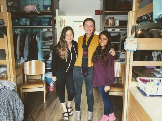 Cassie Murphy stands between two of her friends in a University of San Francisco dorm room. Murphy planned to graduate with nearly zero in student loans, but will now owe almost $15,000 after USF increased tuition three years in a row.