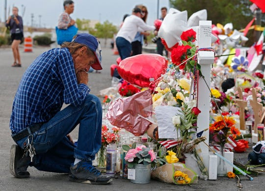 Antonio Basbo kneels in front of the cross for his partner Margie Reckard at the make shift memorial for the mass shooting that happened at a Walmart in El Paso, Texas, Aug. 6,  2019. Twenty two people killed and over forty injured from the mass shooting at the Walmart in El Paso.