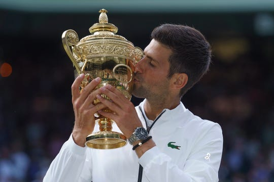 Novak Djokovic poses with the Wimbledon trophy after his match against Roger Federer.