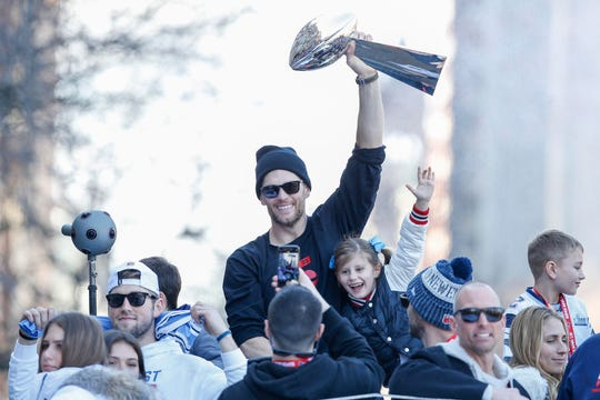 New England Patriots quarterback Tom Brady (12) holds up the Vince Lombardi Trophy during the Super Bowl LIII championship parade through downtown Boston.