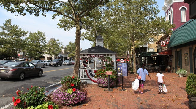 People walk along East Main Street in Freehold Borough Tuesday, August 6, 2019.