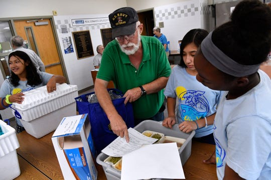 Amir Williams, right, and Ezmi Gonzales with Connecting Caring Communities assist Michael Roche in filling his Meals on Wheels order July 31. Youths from CCC were assisting volunteers with sorting and loading meals.