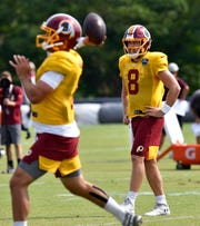 Case Keenum watches fellow quarterback Josh Woodrum throw a pass during the Washington Redskins training camp in Richmond, Va. Monday.