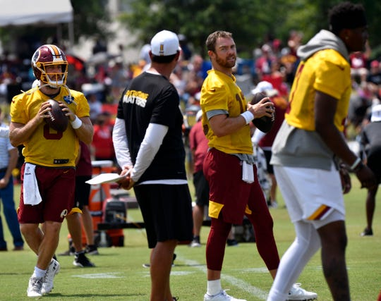 Quarterbacks Case Keenum (left) and Colt McCoy listen to Washington Redskins quarterback coach Tim Rattay during training camp Tuesday in Richmond, Va.