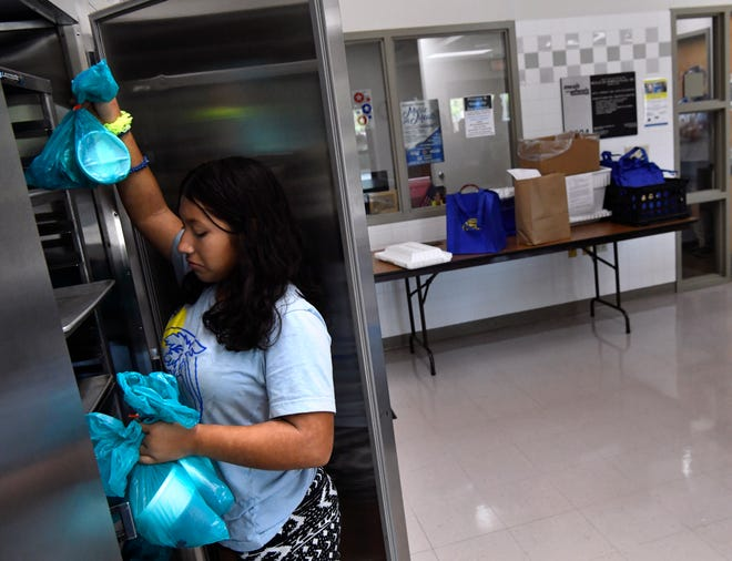 Mariella Vasquez, 11, retrieves bags containing juice and other cold items from a refrigerator at Meals on Wheels Plus on July 31. Youths from Connecting Caring Communities were assisting volunteers with sorting and loading meals.