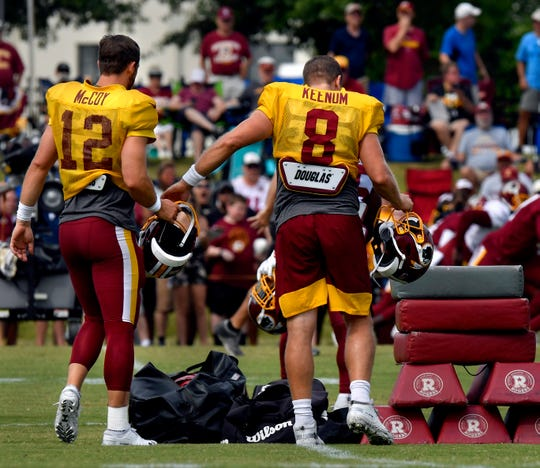 Case Keenum hands Colt McCoy his helmet as the two quarterbacks walk to one of the practice fields Monday during Washington Redskins training camp in Richmond, Va.
