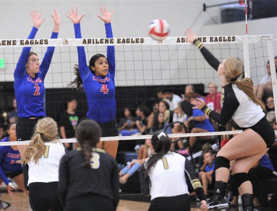 Cooper's Haley Riley (2) and Keiana Kemp (4) defend at the net as an Abilene High player hits the ball. Abilene High beat the Lady Cougars 25-20, 25-21, 18-25, 20-25, 15-10 in the season-opening volleyball match Tuesday, Aug. 6, 2019, at Eagle Gym.