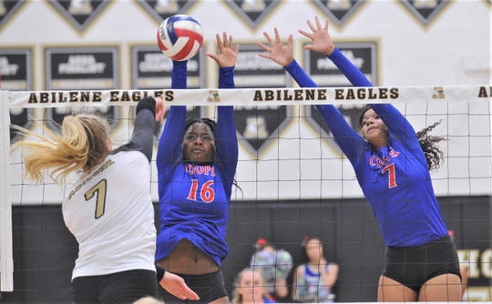 Cooper's Dazz Larkins (16) and Diamond Brown (7) attempt to block a shot by Abilene High's Gentri Anderson (7). Abilene High beat the Lady Cougars 25-20, 25-21, 18-25, 20-25, 15-10 in the season-opening volleyball match Tuesday, Aug. 6, 2019, at Eagle Gym.