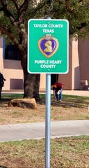 "The road-style sign that was unveiled in a special ceremony Wednesday proclaiming Taylor County to be a ""Purple Heart County."""