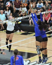 Abilene High's Gentri Anderson, left, hits the ball as two Cooper players defend at the net. Abilene High beat the Lady Cougars 25-20, 25-21, 18-25, 20-25, 15-10 in the season-opening volleyball match Tuesday, Aug. 6, 2019, at Eagle Gym.