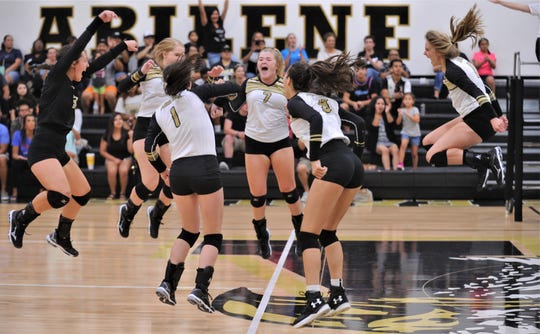 Abilene High players celebrate after beating Cooper 15-10 in the fifth and deciding match in the opening-season volleyball match Tuesday, Aug. 6, 2019, at Eagle Gym. AHS won the match 25-20, 25-21, 18-25, 20-25, 15-10.