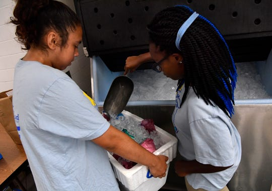 Isabella Culver, 15 (left) and Brittany McNealy, 16, add ice to a cooler at Meals on Wheels Plus July 31, 2019.