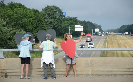 Jeanne Reid, 66, from left, Sandy Wehling, 76, and Dorothy Bosse, 63, all of Battle Creek wave at traffic on Interstate-94 and Capital Avenue Southwest on Wednesday.