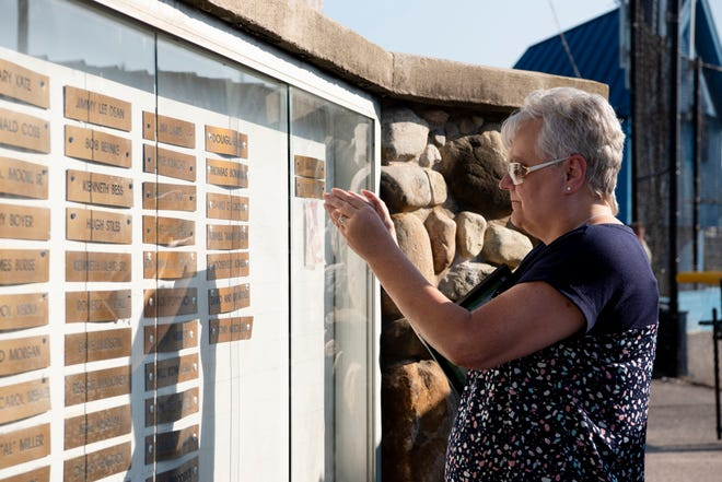 Vicki Gibson checks out her husband Barney Gibson's name on Battle Creek's Wall of Fame on Wednesday, Aug. 7, 2019 at Bailey Park in Battle Creek, Mich.