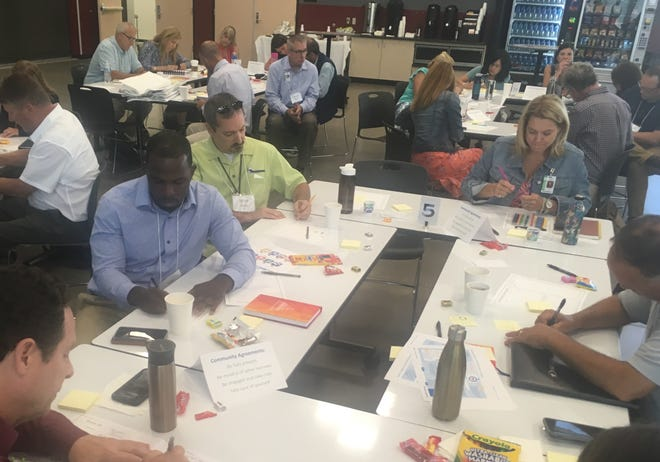 Principals and administrators from Central Kitsap School District work on an exercise about job satisfaction during a workshop on school staff stress and burn-out on Monday. The workshop was presented by Kaiser Permanente.