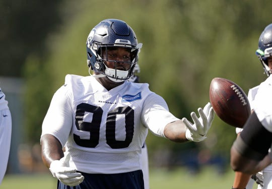 Jarran Reed tosses a football during training camp in August. The Seahawks lineman returns from a six-game suspension this week and should play against Baltimore.