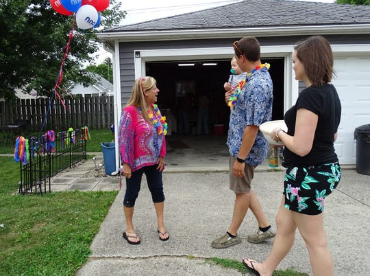 Linda Conti, left, greets Beau Pojman, carrying Emmett Pojman, 9 months, and Cayte Pojman as they arrive at a National Night Out party on Kaler Avenue Tuesday.