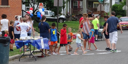Kids and adults attending a National Night Out party at East Street and Woodlawn Avenue, in front of Father's Heart Healing Center, play a game similar to musical chairs on Tuesday. Host Karolyn Rebon provides the music with her cell phone.