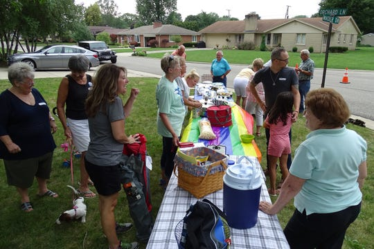 Neighbors greet each other during a National Night Out party at Mader Drive and Orchard Lane on Tuesday.