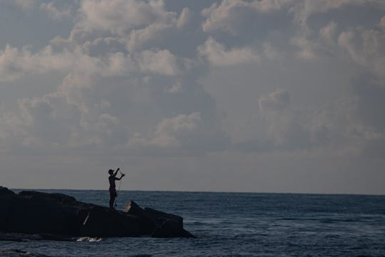 A man stands at end of the Fish Pass jetties at Mustang Island State Park on Friday, Aug. 2, 2019.