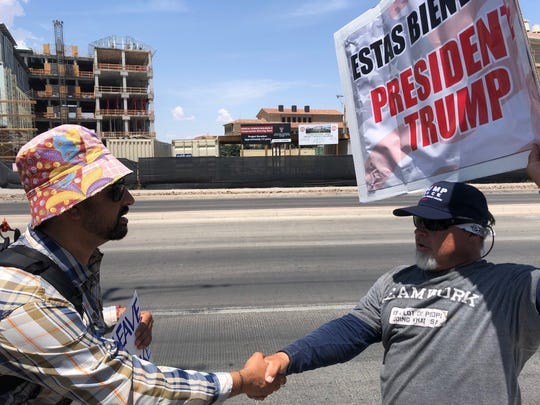 Eduardo Guerrero, left and no fan of the president, shakes hands with President Donald Trump supporter Tony Lee after a civil but disagreeing discussion while waiting for the president to arrive in El Paso, Aug. 7, 2019.