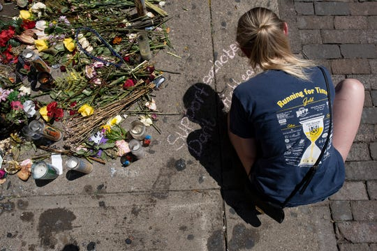 A woman writes in chalk next to a memorial in front of Ned Peppers Bar in the Oregon District of Dayton, Ohio on Wednesday, August 7, 2019 the site of a mass shooting.