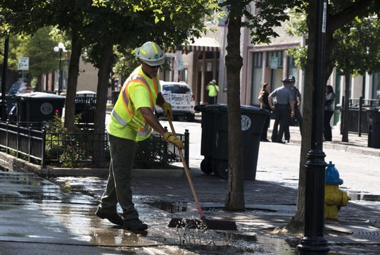 Dayton City workers clean along the 400 block of E. Fifth Street, where a mass shooting that left ten dead, including the shooter, and 27 injured Sunday, Aug. 4, 2019, in Dayton, Ohio.