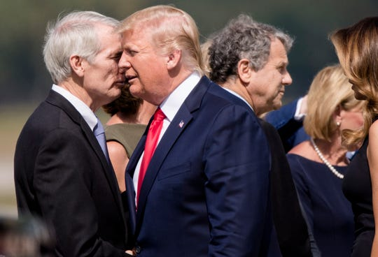 President Donald Trump shakes hands with Sen. Rob Portman at Wright-Patterson Air Force Base, Wednesday, Aug. 7, 2019, as he visits Dayton, Ohio, following the mass shooting that left nine dead and 27 injured early Sunday morning.