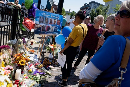 People walk past a memorial in front of Ned Peppers Bar, the site of a mass shooting, in the Oregon District of Dayton, Ohio on Wednesday, August 7, 2019.