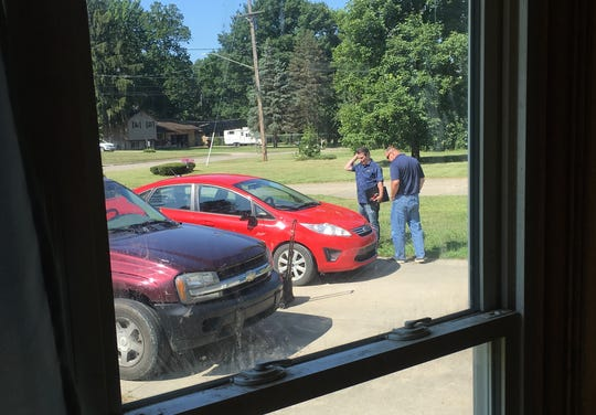 Jerry Cannon (left) and Christopher Kwasniewicz (right) inspect the 2012 Ford Fiesta in the driveway of Michelle Hughes of Flint on Monday, Aug. 5, 2019.