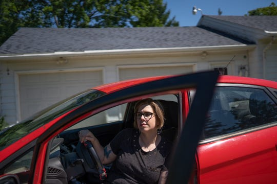 "Michelle Hughes sits in her 2012 Ford Fiesta parked at her home in Flint on Wednesday, June 26, 2019. ""It got me to and from work for quite a few years and now it just sits in the driveway,"" Hughes said, about her car plagued with a transmission problem that only drives when necessary due to safety concerns. ""I trusted Ford and I shouldn't have."""