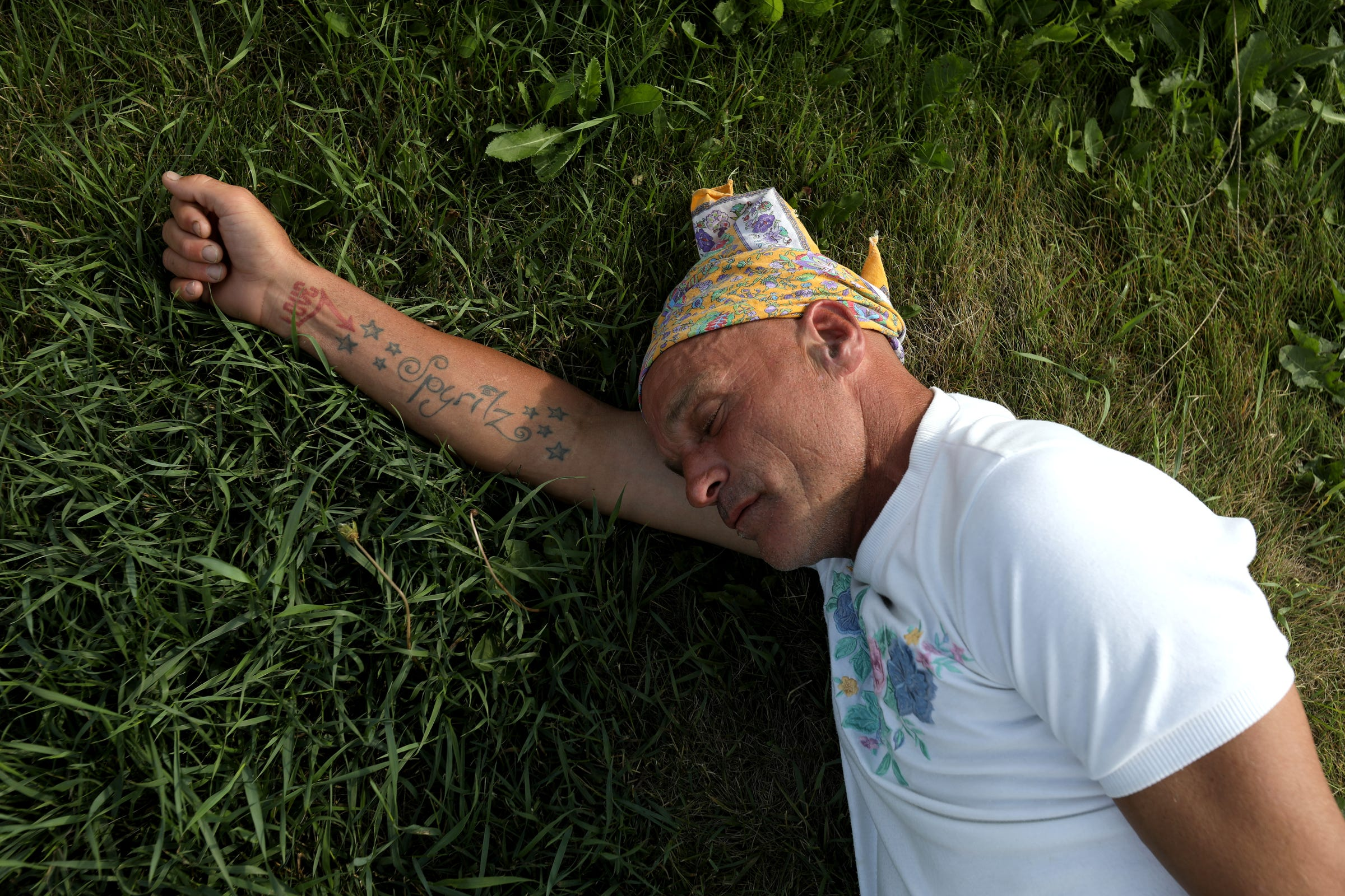 Joe Murphy sleeps underneath the Canadian Tire gas station sign, where many residents of Kenora, Ontario, are used to seeing him. Often people stop by, bringing him food from McDonalds and Tim Hortons, like this man did for him on Wednesday, July 10, 2019