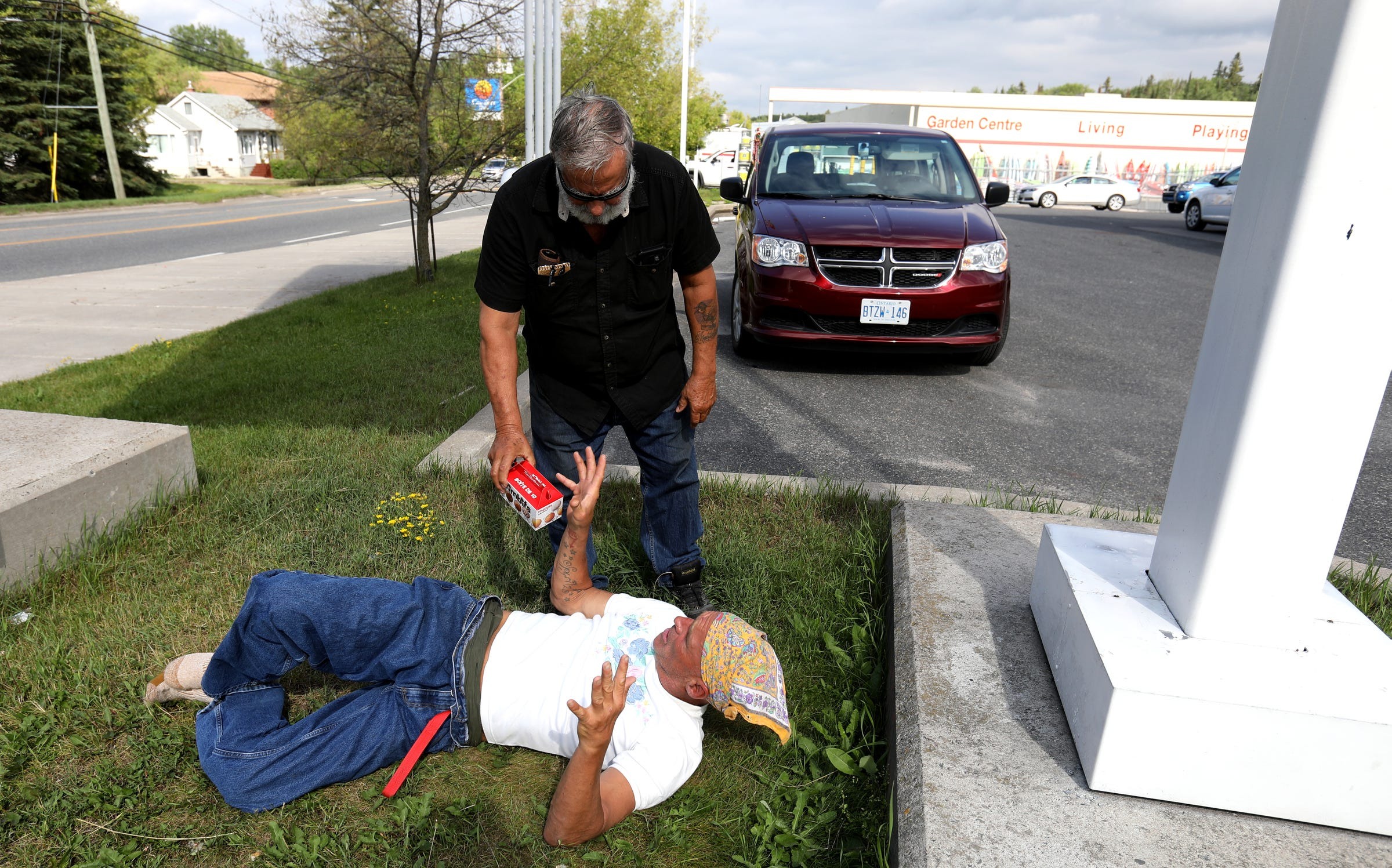 Joe Murphy often returns to sleep underneath the Canadian Tire gas station sign where many residents of Kenora, Ontario, are used to seeing him. Often, people stop by, bringing him food from McDonalds and Tim Hortons like this man did for him on Wednesday, July 10, 2019. After living in a hotel in Kenora, Ontario, Canada set up by former NHL hockey players, former Detroit Red Wings player Joe Murphy is back on the streets of that city and homeless.