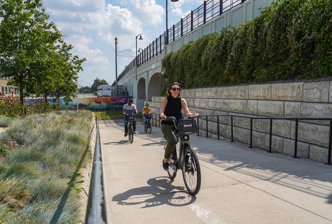 MoGo founder and executive director Lisa Nuszkowski (center) demonstrates the power assist of the new MoGo Boost bike share going uphill along the Dequindre Cut in Detroit on Monday, August 5, 2019.