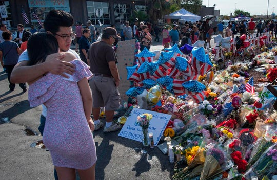 People hug on Aug. 7, 2019, at the makeshift memorial for victims of the shooting that left a total of 22 people dead in El Paso, Texas.
