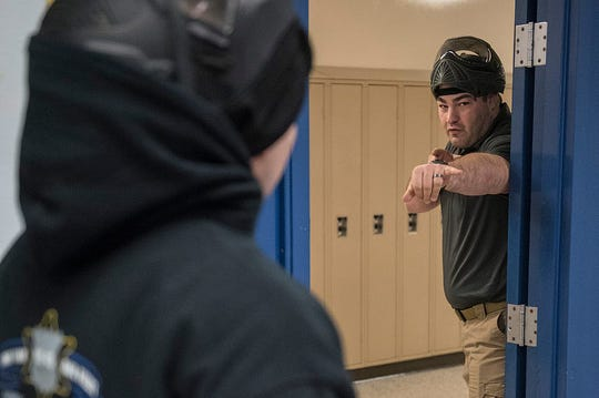 Officer Mike Hinkle debriefs with a fellow officer during a simulated active shooter during training for Plymouth Township police at the Plymouth Arts and Recreation Complex in Plymouth in January 2017.
